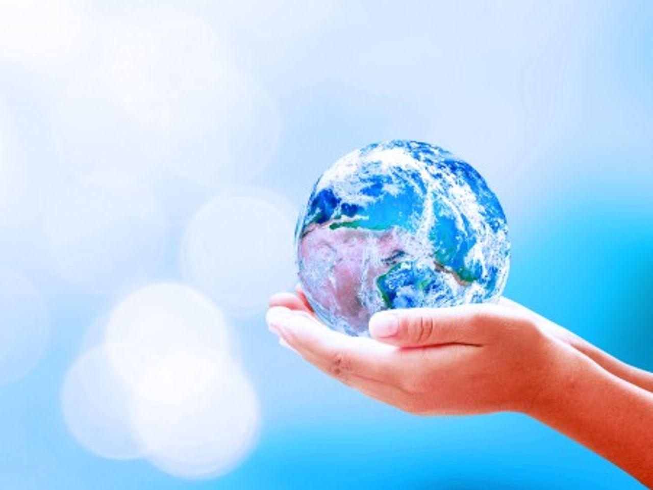 Dve ruky držia v jednej ruke sklenený glóbus na modrom pozadí
